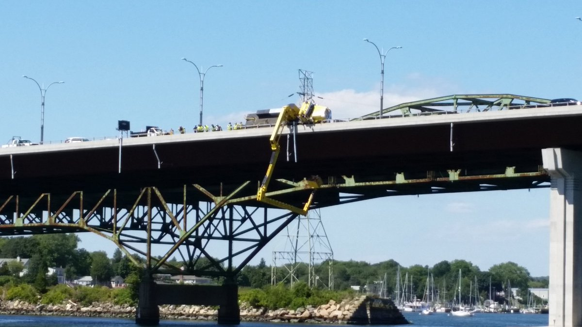Crane truck tips over on Sakonnet River Bridge, traps two workers